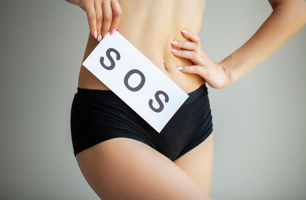 Vaginal or urinary infection and problems . young woman holds paper with sos above crotch