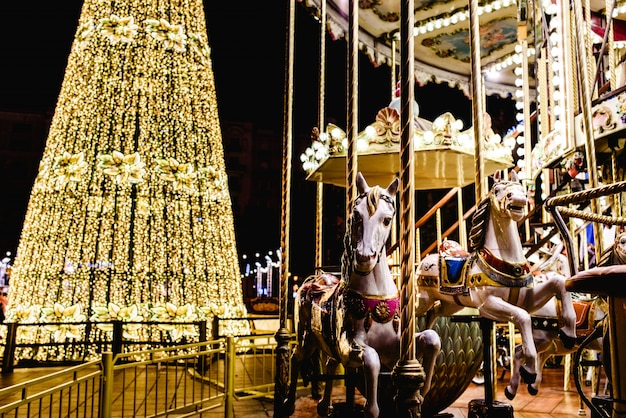 Valencia, spain - january 2, 2018: christmas tree illuminated with led and children's carousel with toy horses, in the city of valencia.