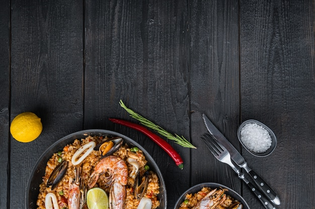 Valenciana seafood paella in bowl and frying pan on black wooden planks, top view with space for text