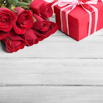Valentine background of gift box and red roses on white wood
