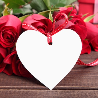 Valentine background of  white gift tag and red roses on wood