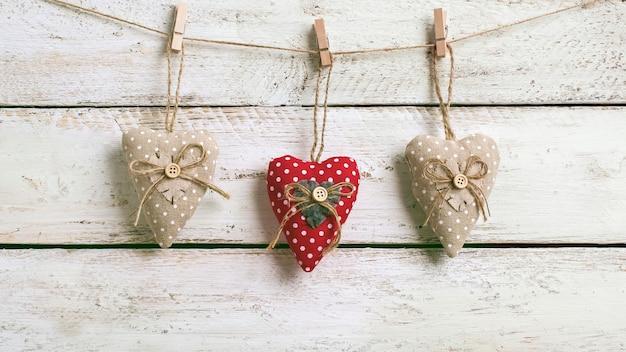 흰색 나무의 소박한 널빤지에 대 한 마음 빈티지 크 래 프 트 clothespins와 발렌타인 배경. 해피 발렌타인 데이 복사 공간