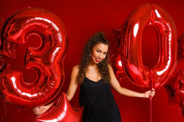 赤い風船を持つバレンタインの美しさの女の子美しい幸せな白人の若い女性の休日のパーティーの誕生日..。
