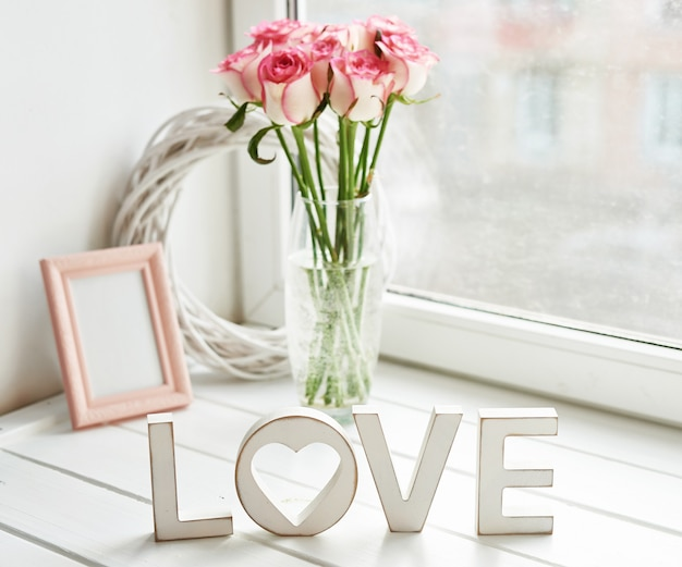 Valentine card. composition with fresh roses and photo frame on window sill. space for text. floral composition with inscription love. mother's day and march 8 card