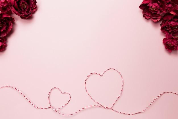 Валентинка. формы сердца. красно-белая веревка или веревка. розы. розовый фон. фото высокого качества