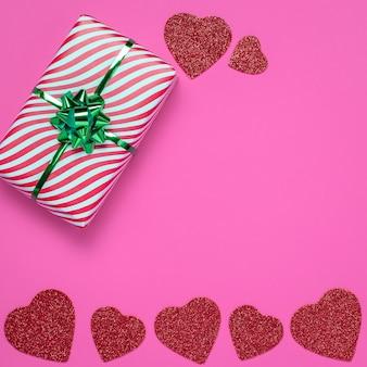 Валентинка или рамка с подарком и красными сердцами на розовом бумажном фоне. символ дня святого валентина, романтического праздника, зимнего праздника любви и привязанности.