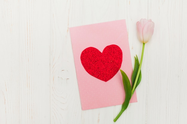 Valentine card with flower on white wooden table