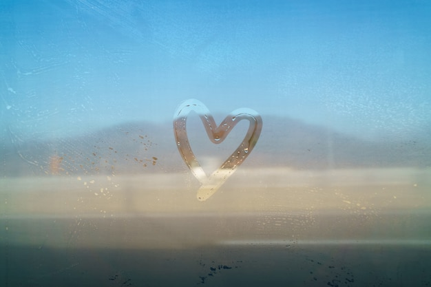 발렌타인 개념 심장 모양의 거울 안개에 손으로 그리기