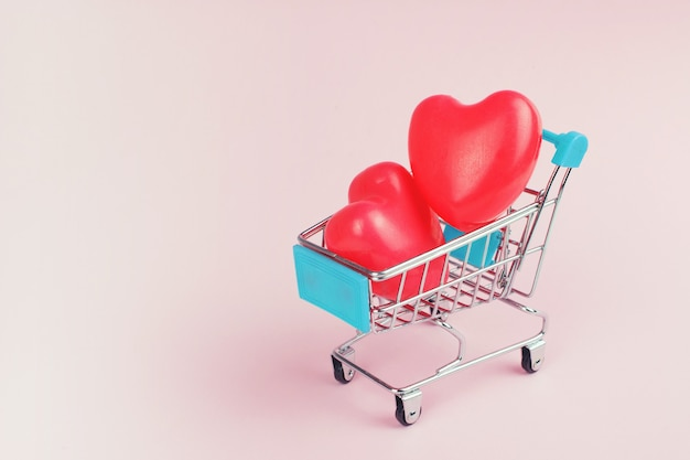 Valentine concept. mini supermarket trolley with red hearts on pink back. shopping lover concept