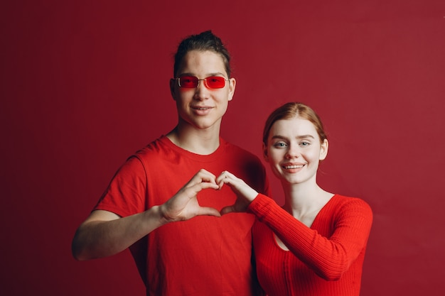 Valentine couple portrait of smiling and hugging making the shape of heart sign with their hands. valentines day