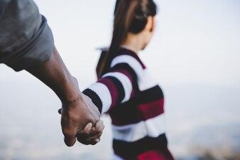バレンタインカップルが手をつないで歩いて、愛を込めてお互いの世話をすることを約束