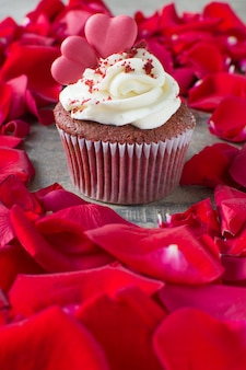 Valentine cupcake surrounded by rose petals on wooden table