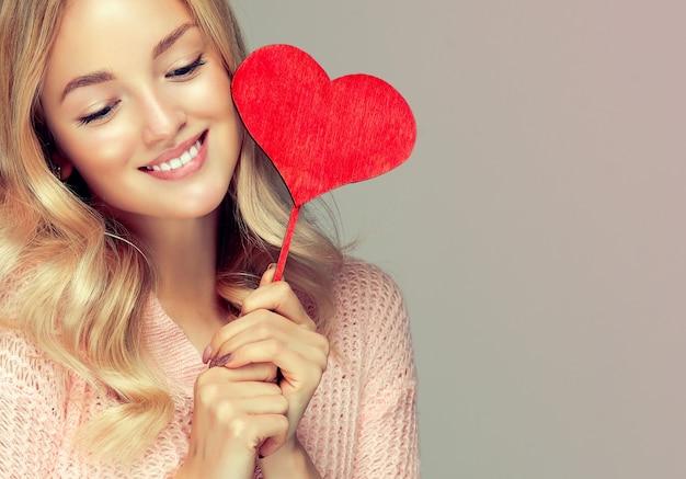 バレンタインデー。魅力的なモデルは、スティックにハートの象徴的なサインを持っています。