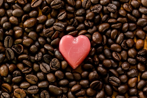 Valentine day background. pink love heart on coffee bean