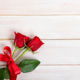 Valentine day background of  red roses on  white wood