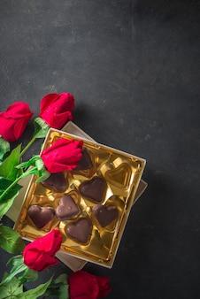 Валентина день фон с шоколадными сердечками и красными розами