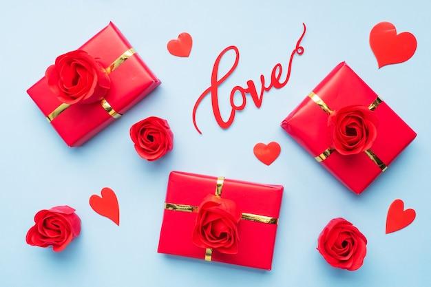 발렌타인 하루 구성, 색종이 하트와 파란색 배경에 장미 인사말 선물 상자. 평평하다.