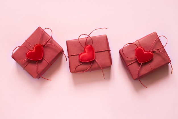 Valentine day composition: three red gift boxes, red rope bows and red hearts on pastel pink . top view.