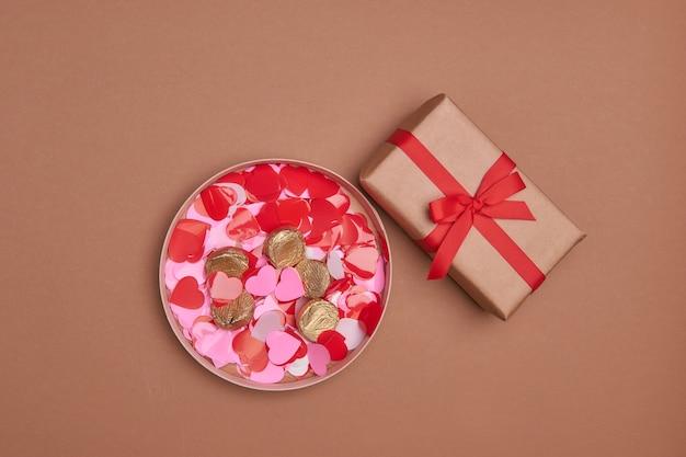 コピースペースのバレンタインデーの構成。リボンの弓と赤いハートのプレゼントまたはギフトボックス。