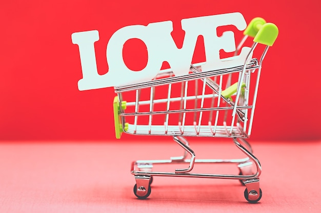 Valentine day concept from word love in shopping trolley on red paper background