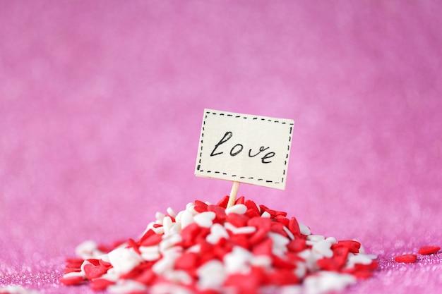 バレンタインデーのコンセプト。ピンクの壁に赤と白のヒープのハートでボード上に構成された愛のテキスト。