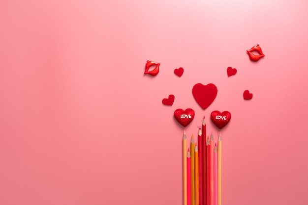 Valentine day concept, red hearts and color pencil on pink background