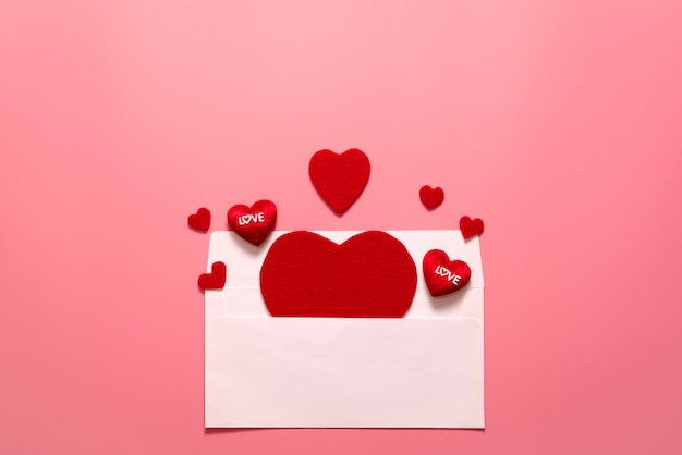 Valentine day concept, red hearts white envelope on pink background