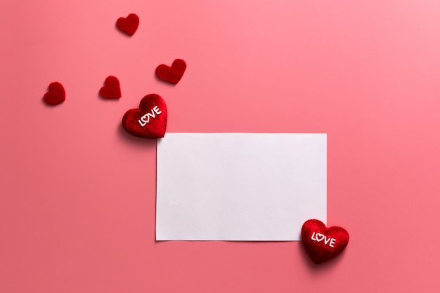 Valentine day concept, red hearts and white note on pink background