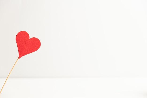 コピースペースと白い背景の上のスティックにハートとバレンタインデーのコンセプト。