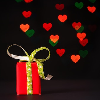 Valentine day concept with a red gift box on a black background with colored heart bokeh