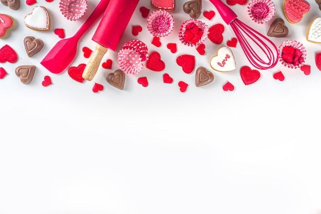 День святого валентина приготовления выпечки фон. посуда и ингредиенты для сладких тортов ко дню святого валентина и печенья в форме сердца