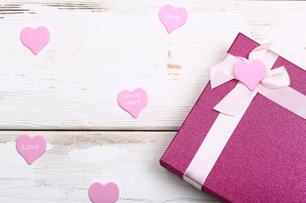 Валентина день дизайн. розовая подарочная коробка с бантом на белом деревянном фоне