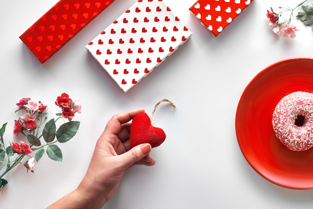 Valentine day flat lay, top view in red, white and green mint colors. geometric two tone split background with white, red and mint green paper. gift boxes, flowers and heart in hand. happy valentine!