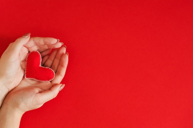 Подарок ко дню святого валентина. вид сверху на сердечко из фетра ручной работы в руке дамы над красным