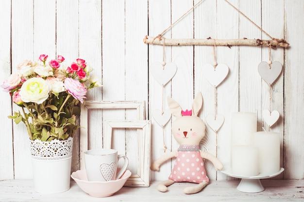 흰색 꽃병에 든 장미, 흰색 머그, 향초, 빈 프레임 및 장난감 토끼와 같은 발렌타인 데이 선물