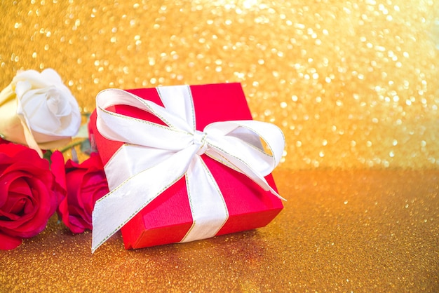 Valentine day greeting card, birthday concept, red gift box with white festive ribbon on golden bokeh background copy space