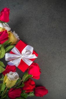 黒いテーブルテーブルに赤いバラの花の花束、ワイン、ギフトボックスとバレンタインデーのグリーティングカード。挨拶のためのスペースのある上面図