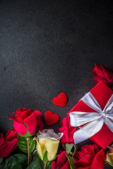 Valentine day greeting card with red rose flowers bouquet, wine and gift box on black table table. top view with space for greetings
