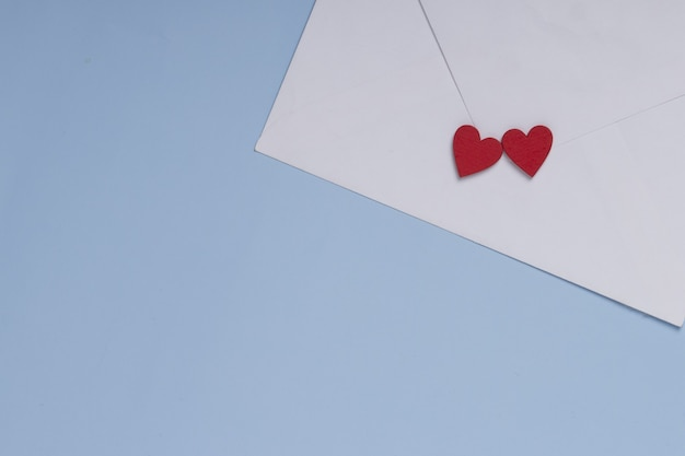 Valentine day greeting concept. envelope and two red hearts on blue background . gift, message for lover.