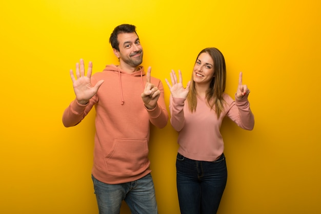 In valentine day group of two people on yellow background counting six with fingers