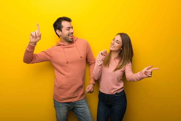 In valentine day group of two people on yellow background enjoy dancing while listening to music at a party