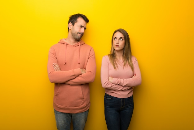 In valentine day group of two people on yellow background feeling upset