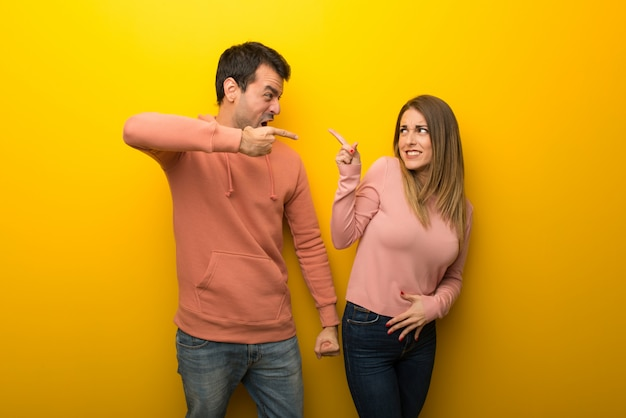 In valentine day group of two people on yellow background frustrated by a bad situation and pointing to the front