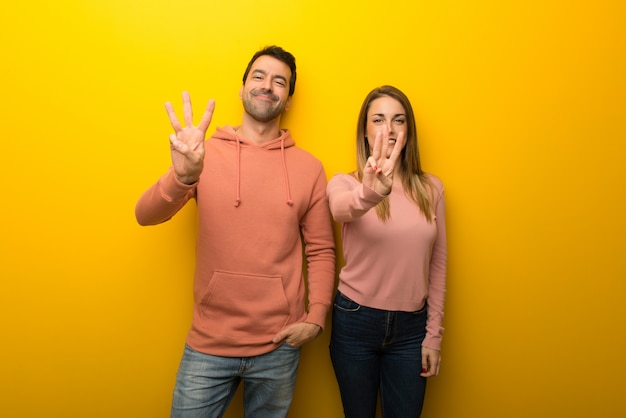 In valentine day group of two people on yellow background happy and counting three with fingers