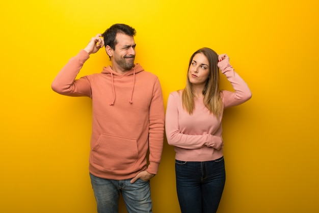In valentine day group of two people on yellow background having doubts while scratching head