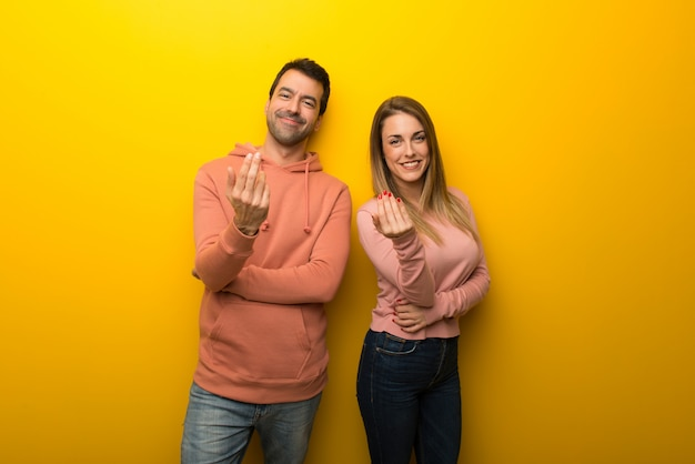 In valentine day group of two people on yellow background inviting to come with hand. happy that you came