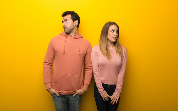 In valentine day group of two people on yellow background is a little bit nervous and scared pressing the teeth