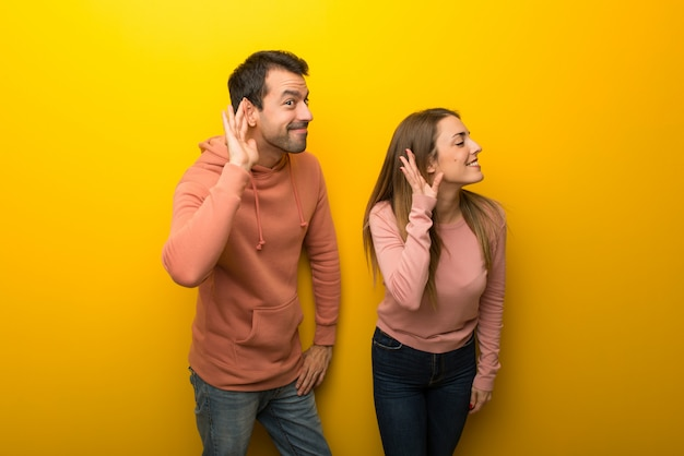 In valentine day group of two people on yellow background listening to something by putting hand on the ear