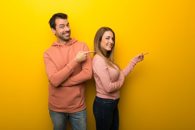 In valentine day group of two people on yellow background pointing finger to the side in lateral position