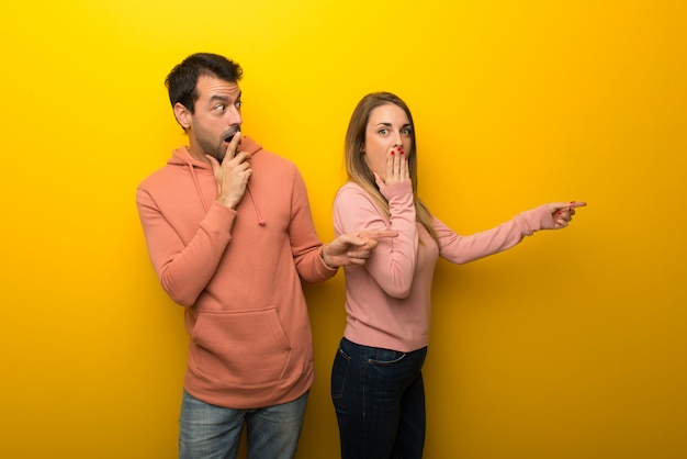 In valentine day group of two people on yellow background pointing finger to the side with a surprised face